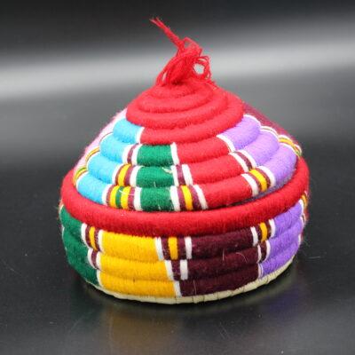 Diese farbenfrohe Dose sieht nicht so aus, ist jedoch aus Bast geflochten. Dabei wird der Bast mit Wolle umwickelt.