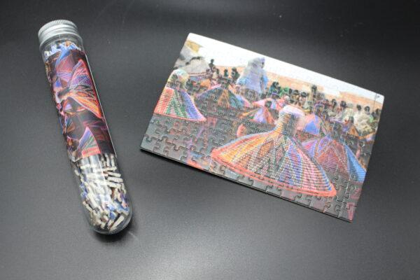 Sie kaufen ein Röhrchen mit 150 Puzzleteilen – wenn Sie fertig sind, haben Sie ein Kunstwerk in Postkartengröße!